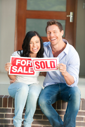 Happy couple holding for sale and sold signs